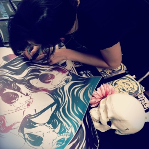 Tina at her table at IE Zine Fest, signing a wheatpaste for me.